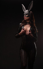 portrait of sexy young woman posing in rabbit mask and bodysuit.