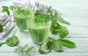 Glasses of fresh vegetable juice on wooden background