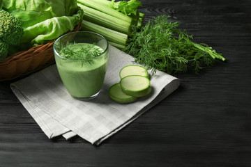 Glass of fresh vegetable juice on wooden background