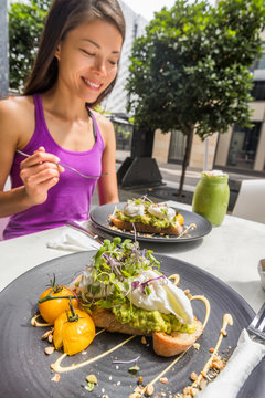 Restaurant breakfast brunch avocado toast with eggs woman eating plate at cafe. Two meals couple enjoying morning together on outdoor street terrace.