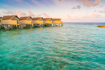 Beautiful water villas in tropical Maldives island at the sunrise time .