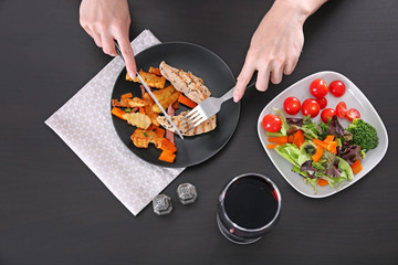Woman eating grilled chicken meat with vegetables at table
