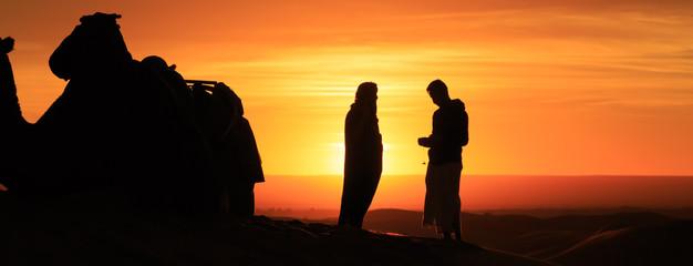 silhouette of men standing in the desert at sunset