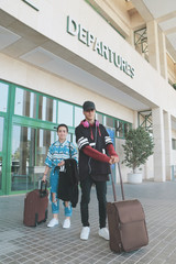 A boy and a girl arriving at the airport with their bags to start a trip