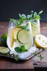 Refreshing cold iced mint drink with lemons and lime, summer drink with ice, selective focus, toned image