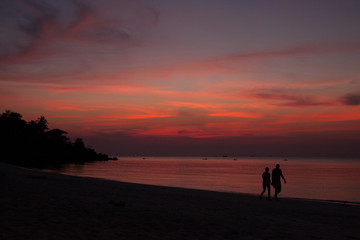 Tropical sunset beach with couple silhouette. High contrast
