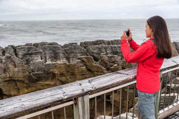 New Zealand travel tourist girl taking smartphone pictures with phone app at Punakaki Pancake Rocks. Woman in Paparoa National Park, West Coast, South Island, New Zealand
