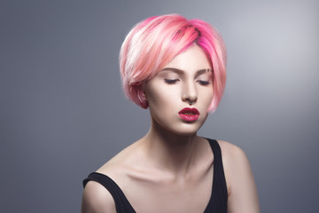 Beauty portrait of a sexy girl with pink hair on a gray background.