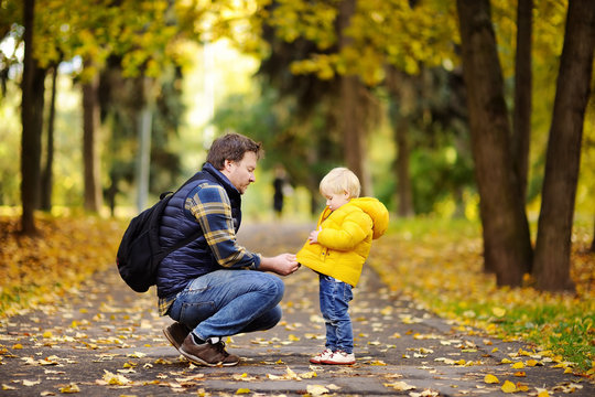 Father and his toddler son walking in autumn park
