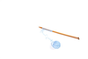 Knitting needles and blue yarn ball on white background