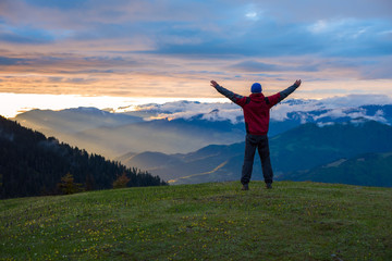Happy traveler with open arms admiring fantastic sunset