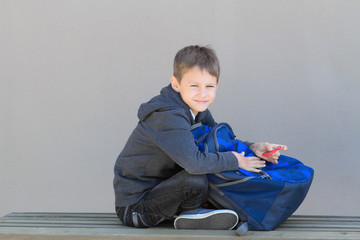 Boy with backpack sitting on the bench after school