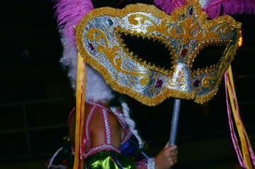 Pretty carnival costumes and feathers of unrecognizable dancers at night time festive background