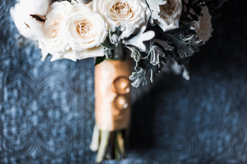 Couple close-up of engagement gold wedding rings on the background of an elegant bouquet of flowers
