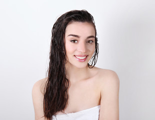 Young woman in towel after shower on white background