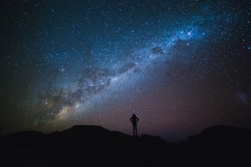 Landscape with Milky Way. Night sky with stars and silhouette of a standing woman on the mountain.
