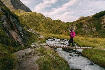 Wanderer auf einer Brücke über einen Bach am Stubaier Höhenweg, Österreich