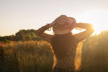 Young bohemian styled woman in nature at sunset