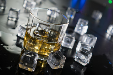 Close up whiskey in glass with ice cubes.dark black background.