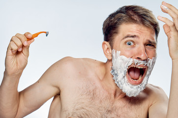 Man with a beard on a white isolated background holds a razor