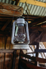 The old rusty kerosene lamp hangs on the nail in a half-ruined wooden building