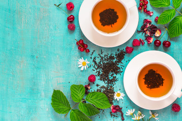 Fresh tea and natural ripe berries on a turquoise background
