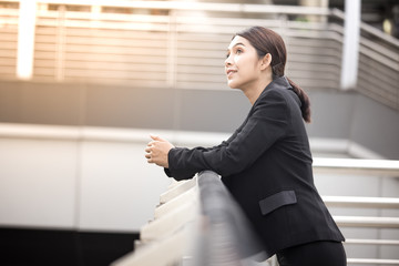 Young Beautiful Asian woman in city looking out and thinking about work. Young business woman with leader concept. White female thinking about business concept.