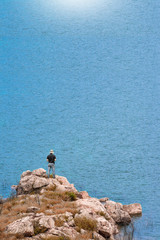 man standing on the rock near the blue sea