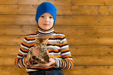 Boy in a blue hat playing with a kitten against a wooden wall background