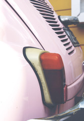 Tail light on a retro car. Car color is pink and a yellow wall in the background. Image has a vintage effect.
