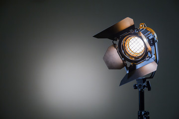Halogen spotlight with a Fresnel lens. Spot light on the wall. TV, video, photo, shooting. Lighting equipment. The light spot on the gray wall