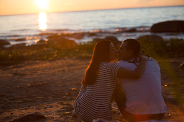 A young couple in love, on the shore of the Bay at sunset