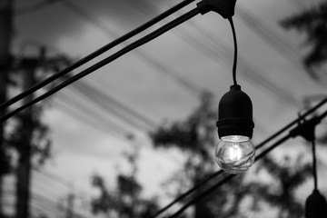 Old light bulb glowing in the dark. Black and white image. (vintage or retro style)