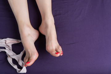 Female feet lie on a purple sheet with thong next to it