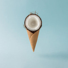 Coconut with ice cream cone on pastel blue background. Foos creative concept.