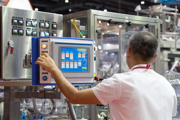 factory engineer controlling and pressing important technology button at control panel of an automatic machine in the manufacturing.
