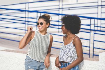 Pretty female friends standing outside talking