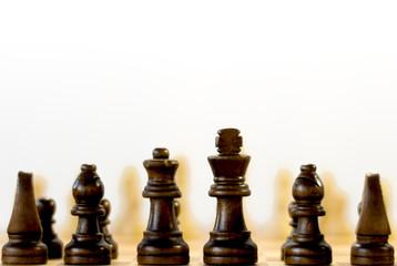 Schwarze Schachfiguren von Hinten mit Schatten von den Weissen Figuren im Hintergrund ,Selektiv Fokus