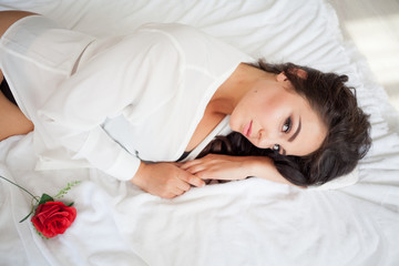 girl in lingerie lying on a bed with a rose