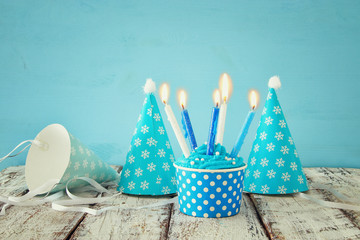Birthday concept with cupcake and candles on wooden table