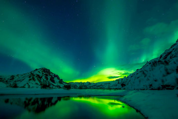 Snowy Mountains at night with northern lights