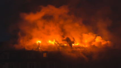Building in fire at the night , burning fire flame with smoke on the apartment house roof