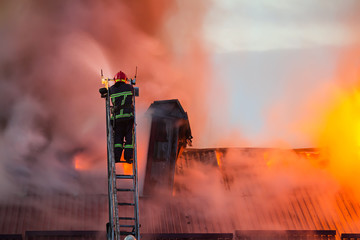 Firefighter or fireman on the ladder extinguishes burning fire flame with smoke on the apartment house roof