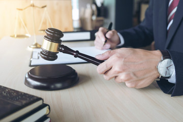 Close up of hand, Judge hitting gavel and scales of justice, Books, Report the case with note paper on wooden table, Law and justice concept