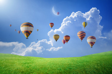 Poster Ballon Hot air balloons flying in blue sky above green field