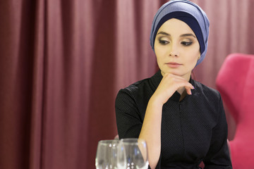 Portrait of a beautiful muslim woman at a table in a restaurant