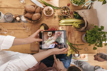 Friends cooking together taking picture of prepared vegetables with tablet, top view