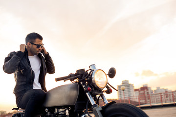 Handsome rider guy with beard and mustache smoking cigaret and correct biker jacket sit on classic...