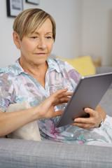 ältere frau sitzt auf dem sofa und tippt auf ihrem tablet