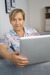 moderne ältere frau sitzt auf dem sofa und arbeitet am laptop